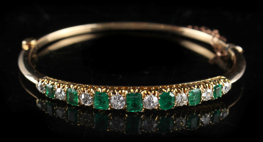 Lot 237 - A Victorian yellow gold emerald & diamond hinged bangle, circa 1890, set with seven graduated