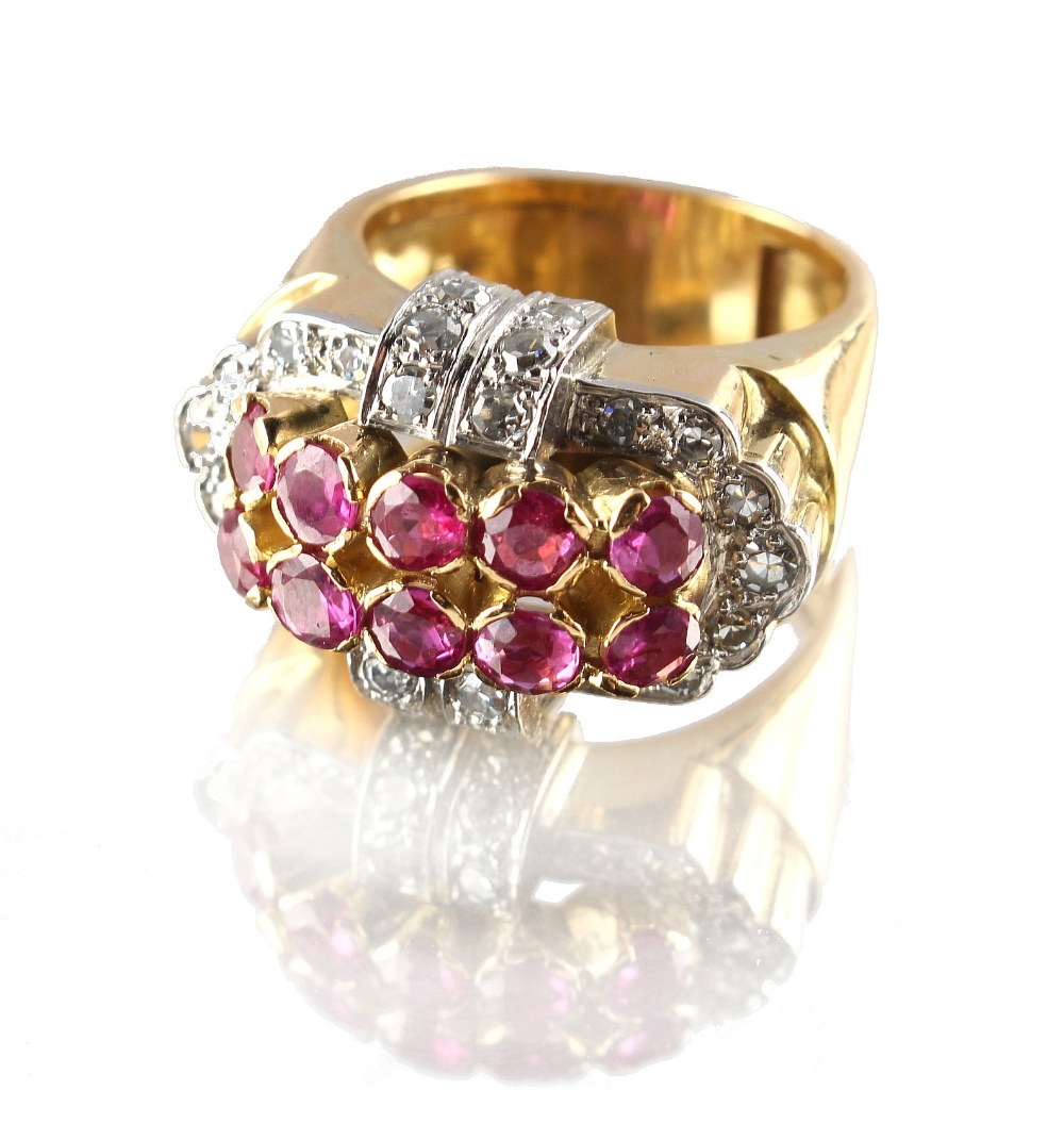 Lot 219 - A modern heavy unmarked yellow gold ruby & diamond buckle ring, the ten round cut rubies weighing an