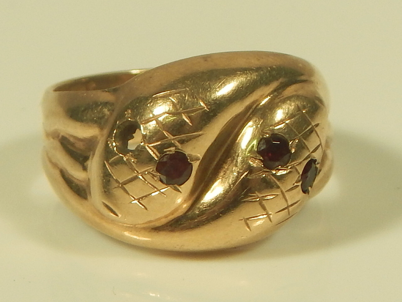 a 9ct gold snake ring with garnet one missing 4