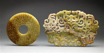 Lot 5028 - (lot of 2) Chinese hardstone archaistic items, the first a bi-disc carved with stylized scroll