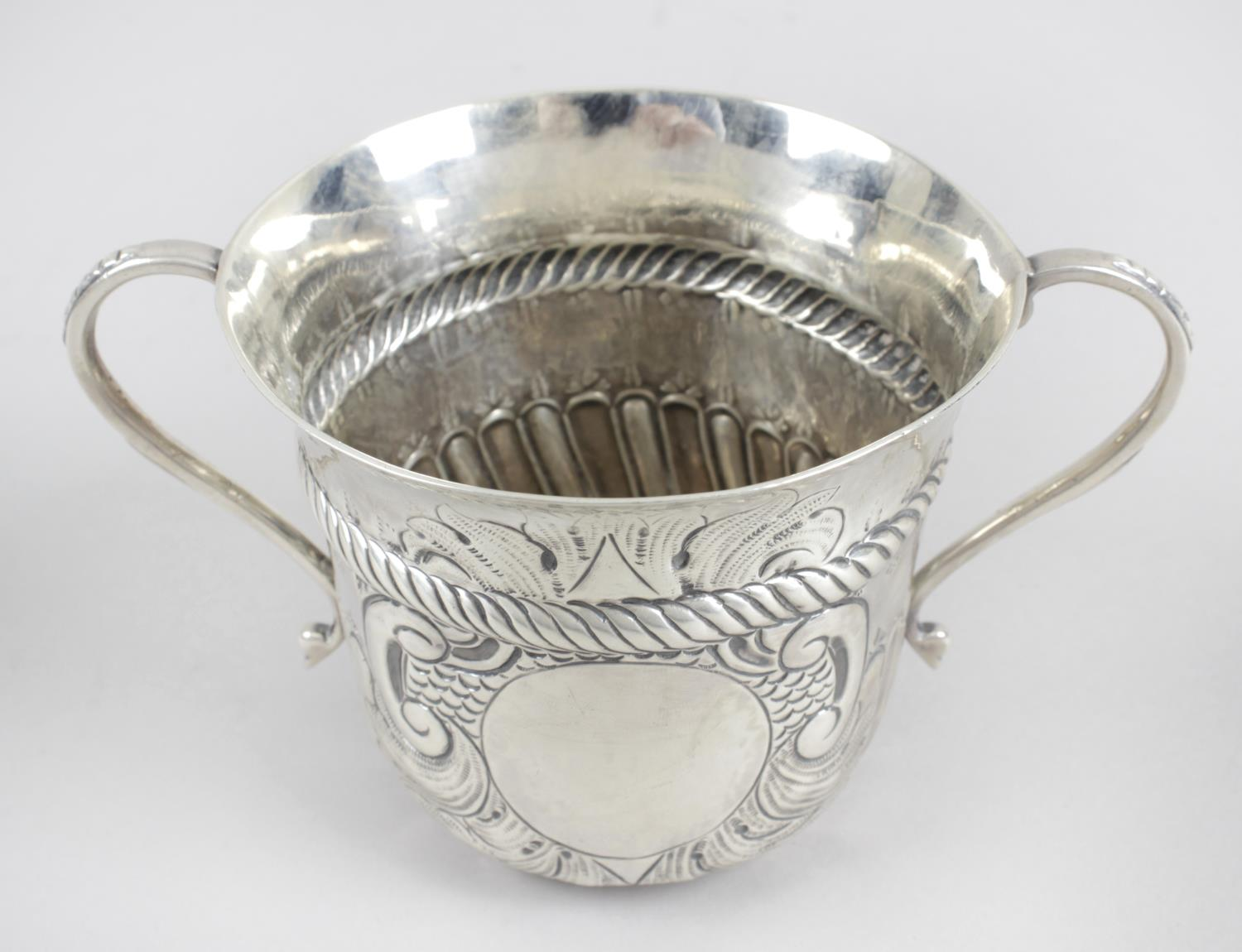 Lot 28 - An Edwardian silver cup of cylindrical form with flared rim and twin curved handles,