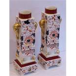 A pair of late 19th century pottery vases hand-gilded and decorated in the Imari palette; each