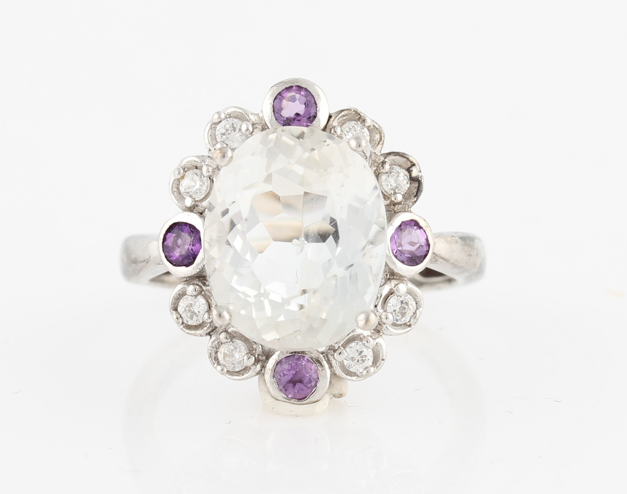 Lot 54 - A topaz and amethyst dress ring, set with a central oval cut colourless topaz surrounded by a border