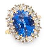 A 7.40 CARAT CEYLON NO HEAT SAPPHIRE AND DIAMOND CLUSTER RING in 18ct yellow gold, set with an