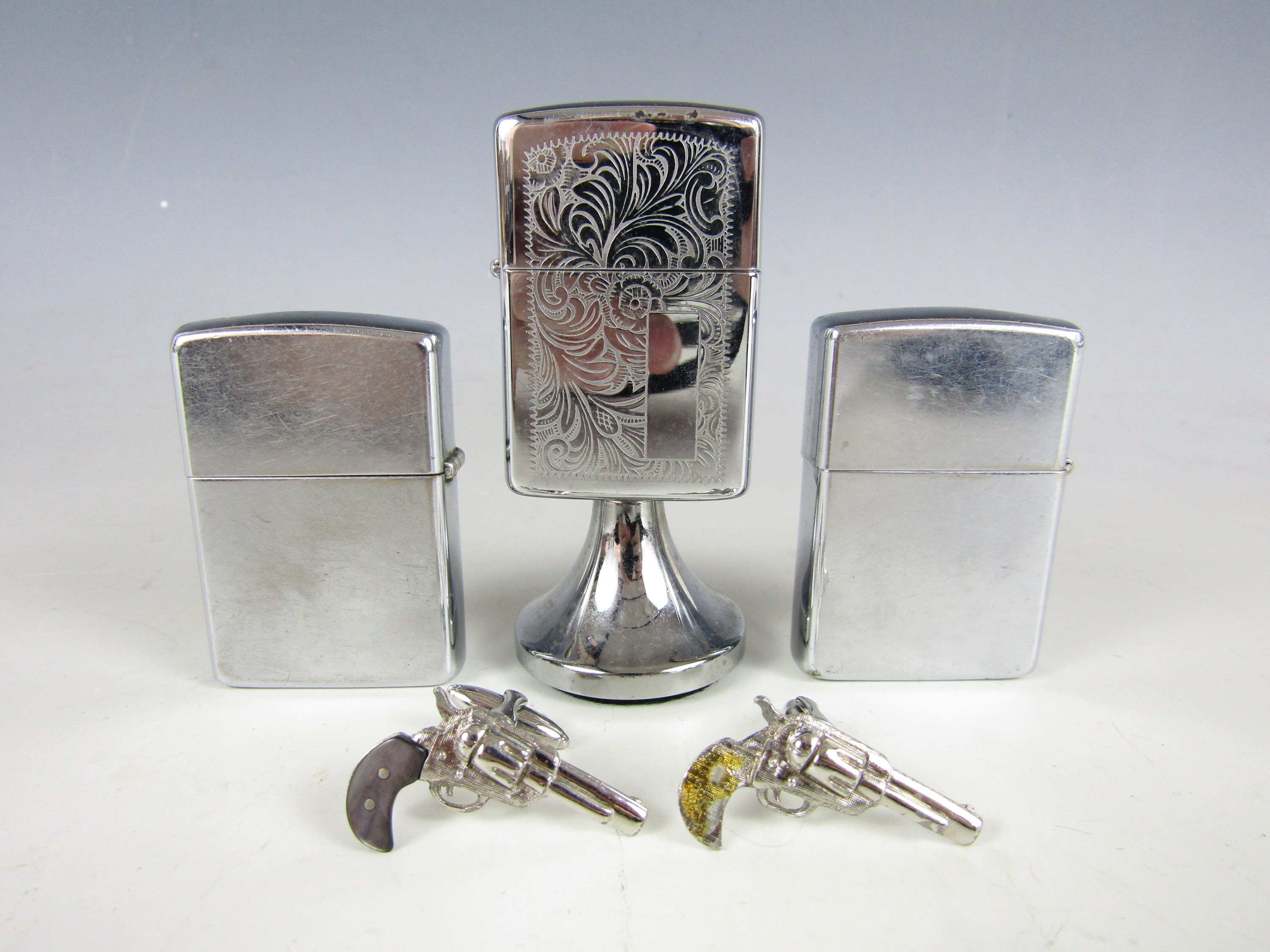 Lot 43 - A Zippo Airborne Special Forces lighter, together with two others, and a pair of novelty cuff