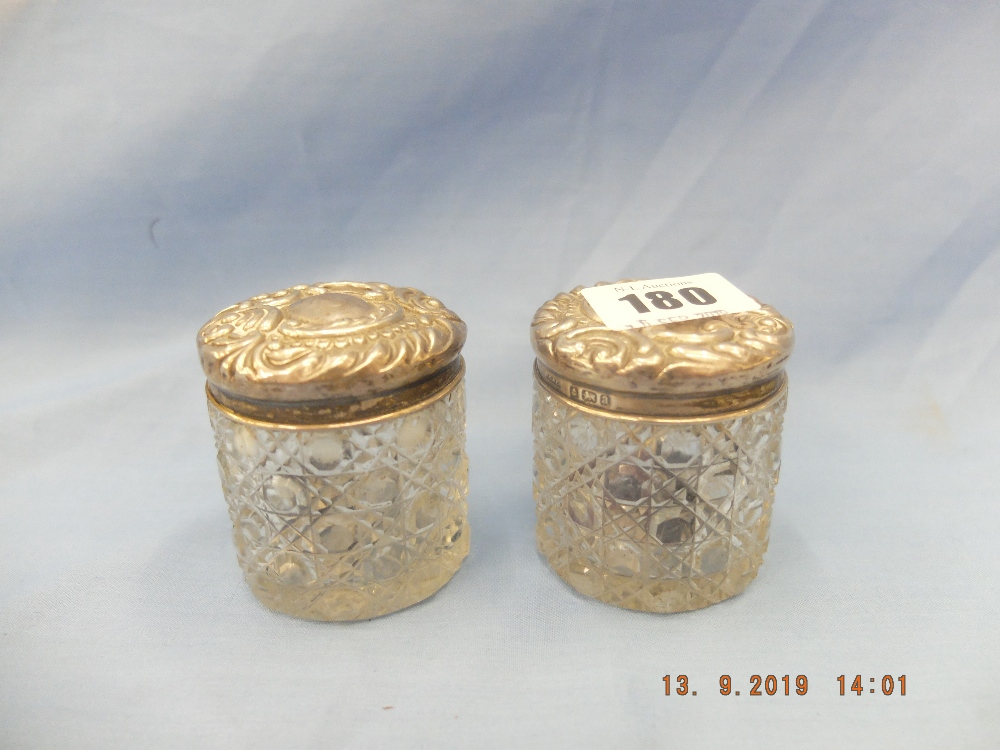 Lot 180 - A pair of cut glass hallmarked silver lidded vanity jars