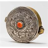 GAU AMULET CONTAINERSilver, brass, coralTibet, late 19th centuryBalanced, circular form, the size of