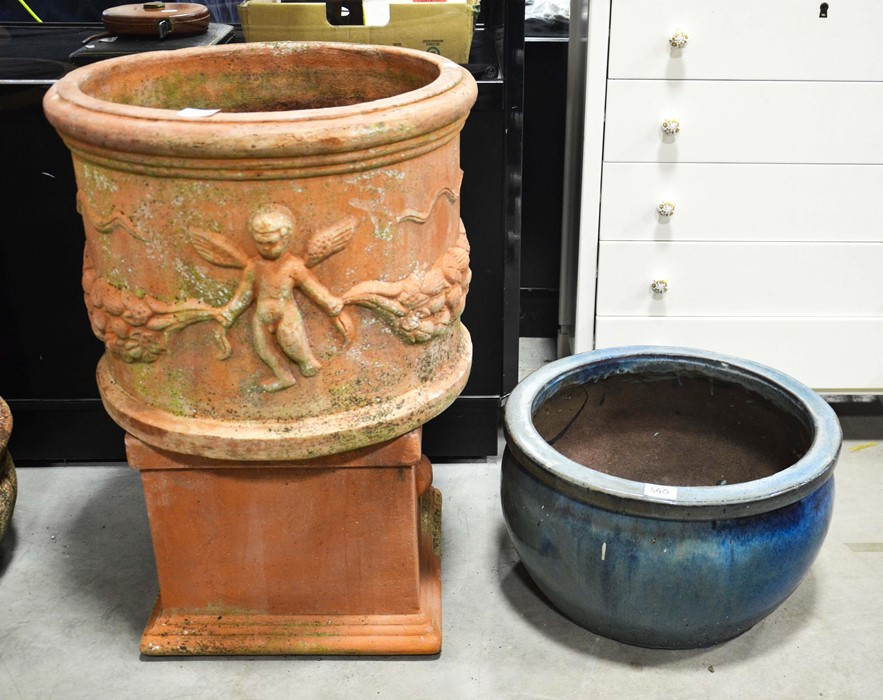 A terracotta circular planter with cherub moulded frieze 50cm diameter , a terracotta pedestal and