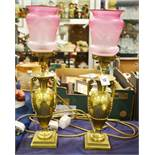 A pair of lacquered brass oil lamps with rose glas