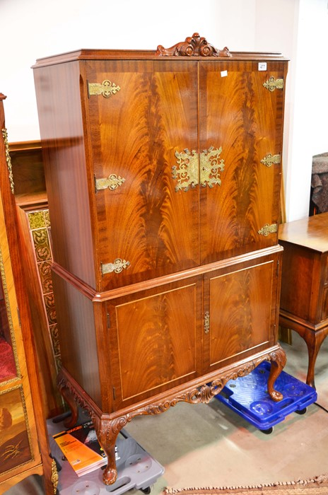 Lot 477 - A flamed twin door cocktail cabinet with fittings, above two cupboard doors, with metal mounts