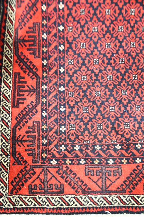 Lot 320a - A red and black geometric borders and foliate central panel