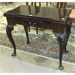 A mahogany fold-over card table in the George II style, the top with recess counter dishes above a