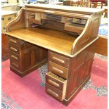 An early-20th century oak knee-hole roll-top desk, revealing pigeon holes and drawers.