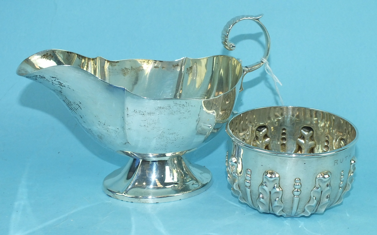 Lot 444 - A silver sauce boat of hexagonal form with scroll handle and loaded base, 12cm high, London 1911,