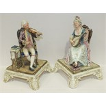 A pair of 19th century Royal Dux Bohemia porcelain figures of seated musicians playing a violin, (
