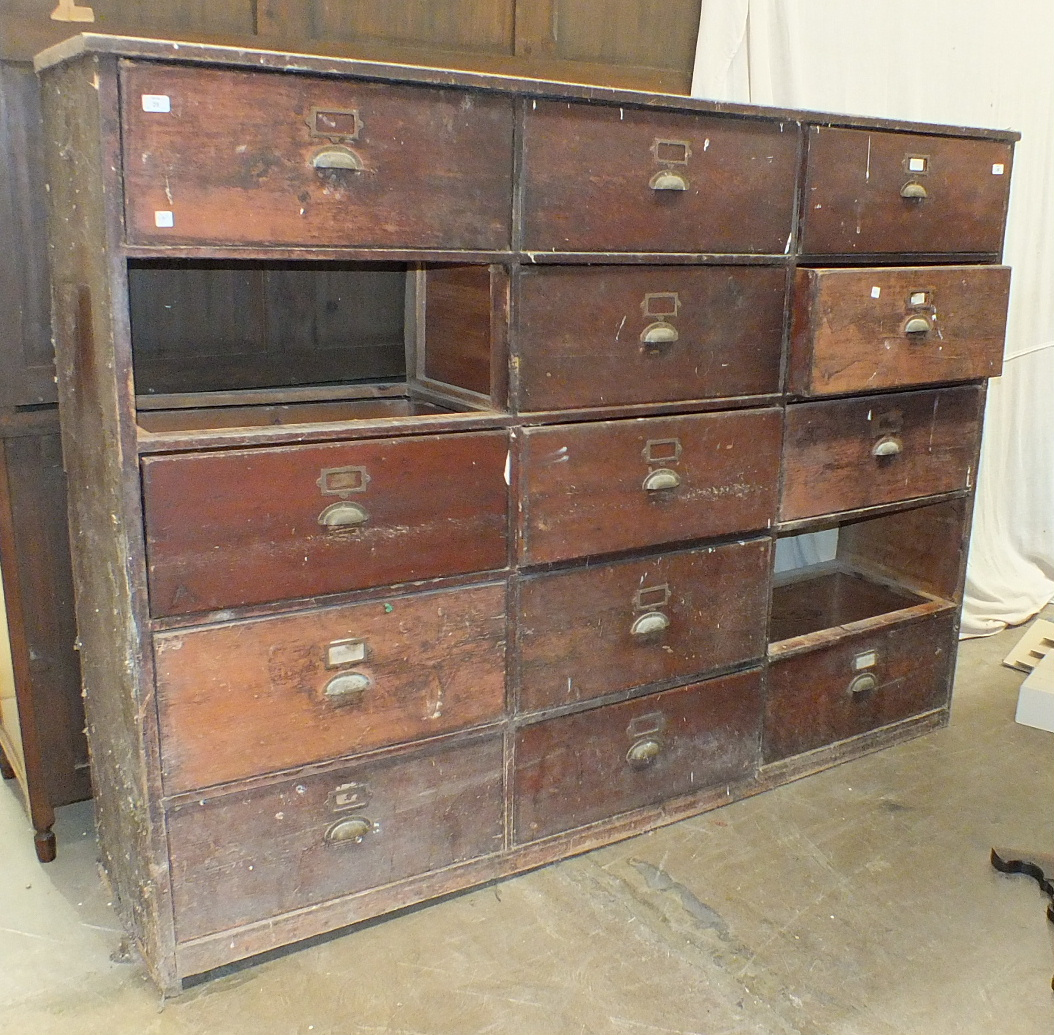 An early-20th century rack of fifteen pine drawers, (two lacking), 216cm wide, 157cm high.