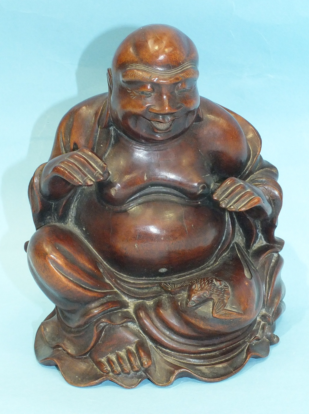 A large 19th century Chinese carved wood figure of a portly Poutai, seated and with a bat on his