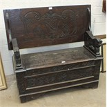 An early-20th century carved oak monk's bench with folding back and lift seat, 106cm wide.