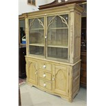 A 19th century pine kitchen dresser, the moulded cornice above two glazed doors, with applied Gothic