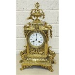 An early-20th century French polished brass mantel clock, the elaborate case with urn finial,