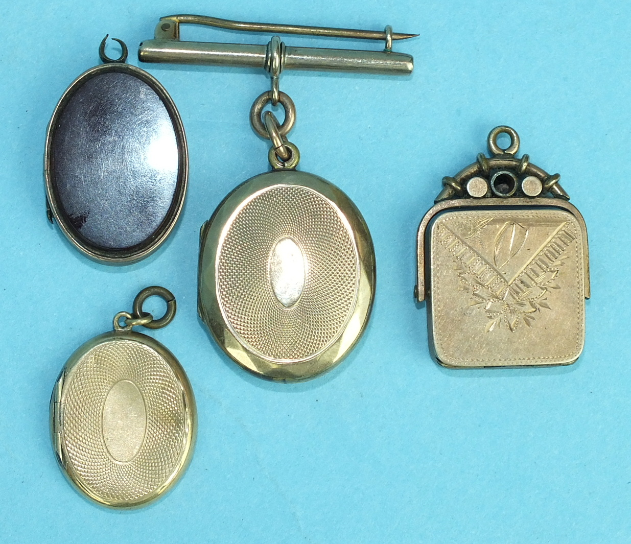 Lot 288 - A Victorian swivel locket with engraved decoration and three other lockets, (4).