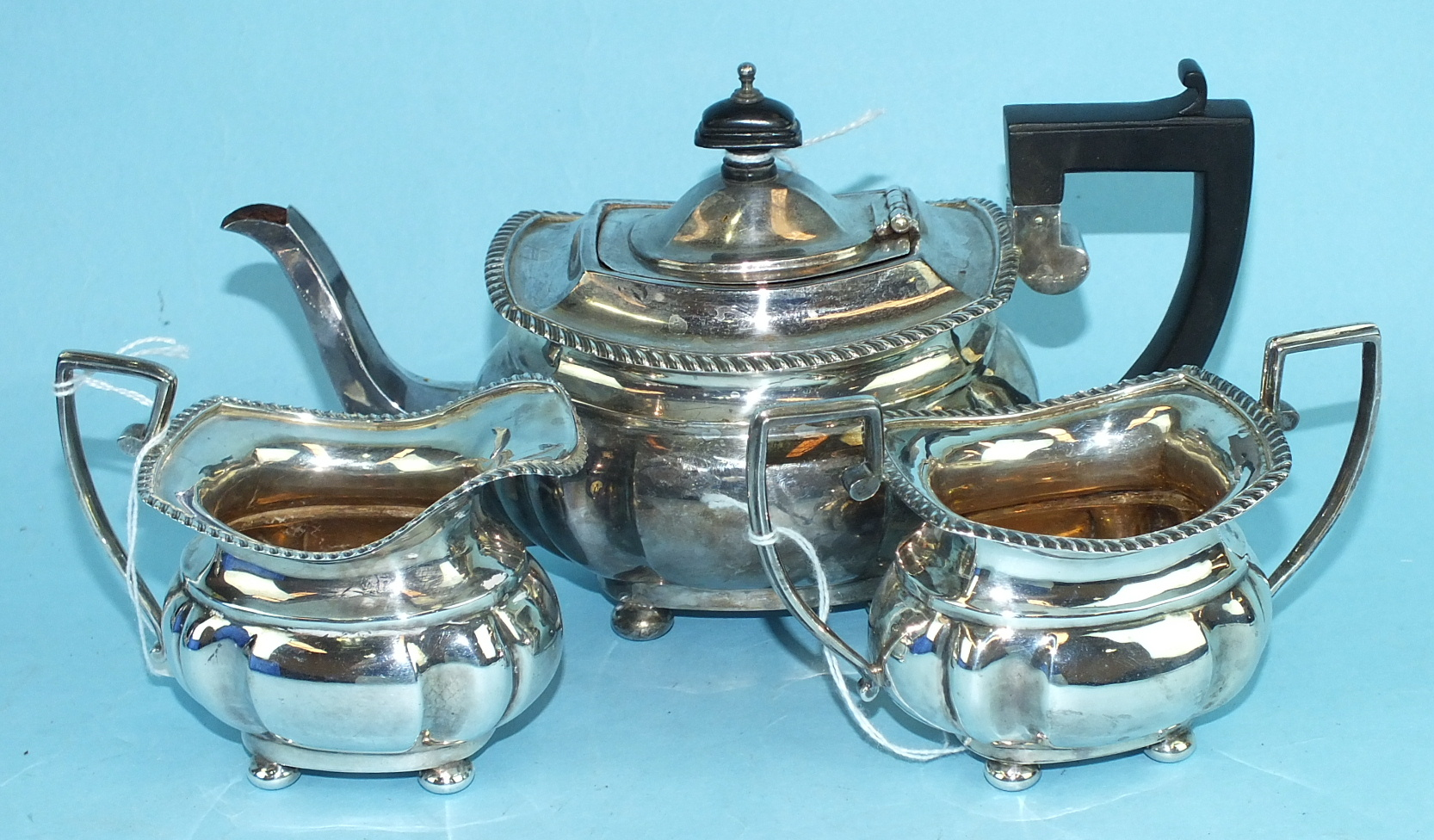 Lot 423 - A bachelor's silver three-piece tea service of shaped rectangular form, with gadrooned edge,