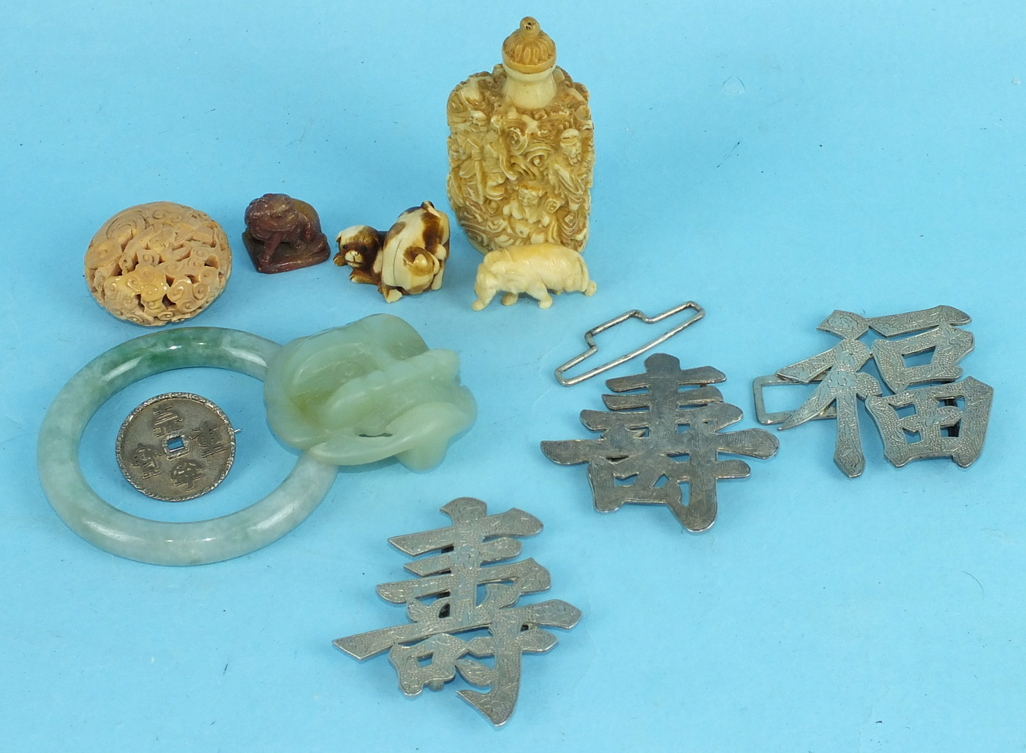 A collection of Oriental works of art, including a Chinese jadite bangle, an animal mask buckle, two