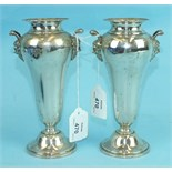 A pair of silver tapering flower vases, each rounded body with Bacchus mask handles, on circular