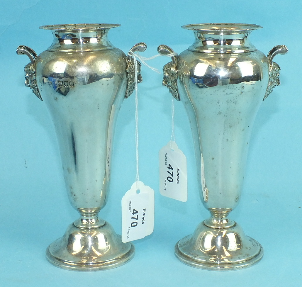 Lot 470 - A pair of silver tapering flower vases, each rounded body with Bacchus mask handles, on circular