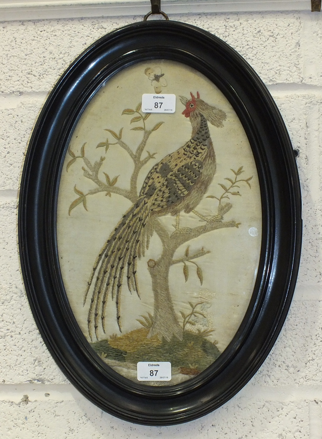 A 19th century oval embroidered silk picture of a pheasant perched in a tree, 38 x 23cm, (old