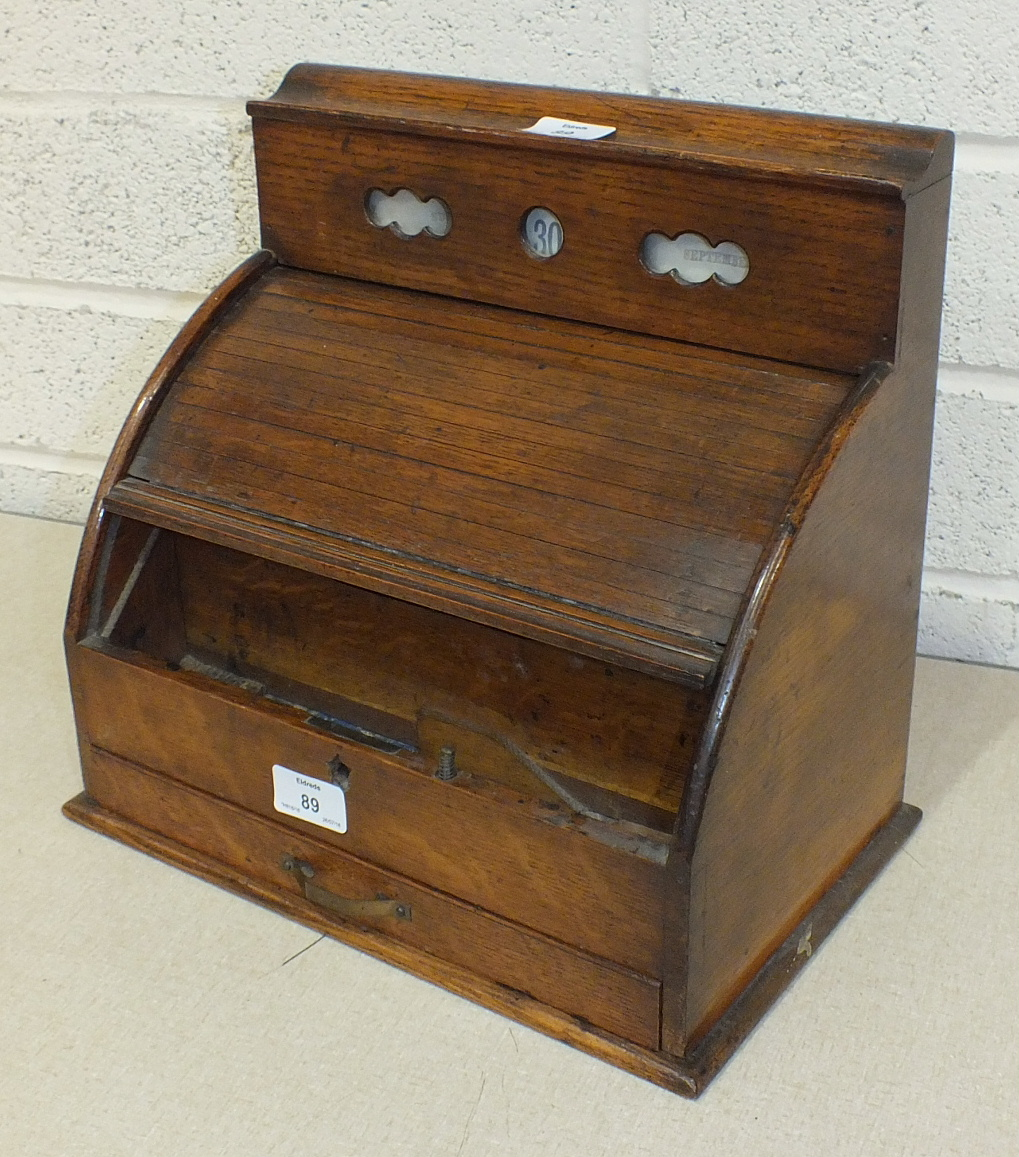 An Edwardian oak stationery box, the perpetual calendar above a tambour front, with fitted