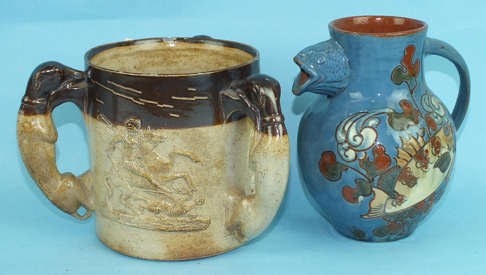 A Brannam Pottery slip-decorated fish jug and a 19th century stoneware tyg with St George & Dragon
