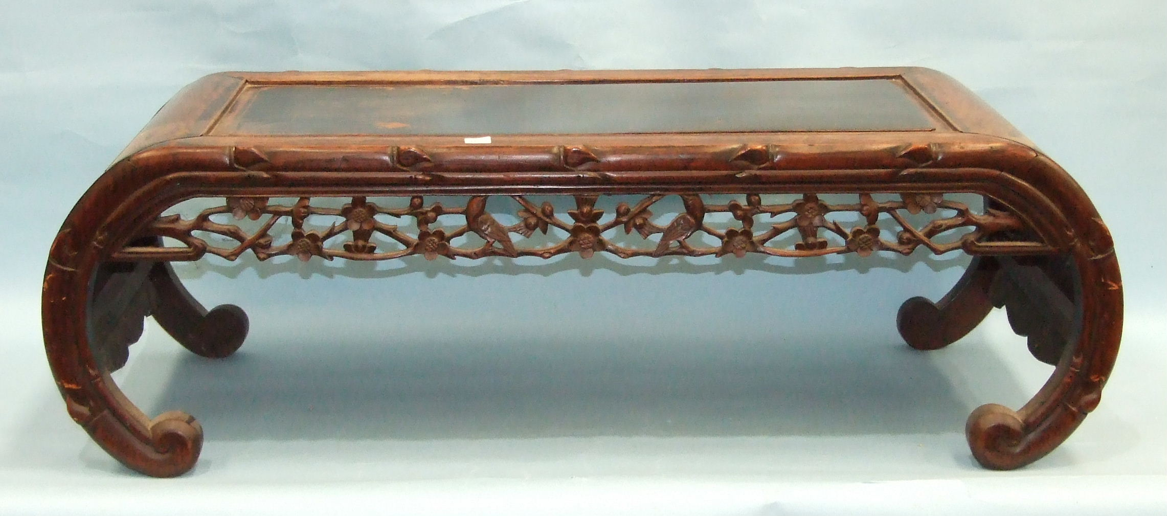 A Chinese hardwood low occasional table with pierced prunus frieze, on scroll supports, 101cm wide.