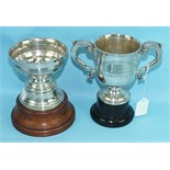 A silver two-handled trophy cup with leaf-capped handles and spreading foot, on ebonised base,