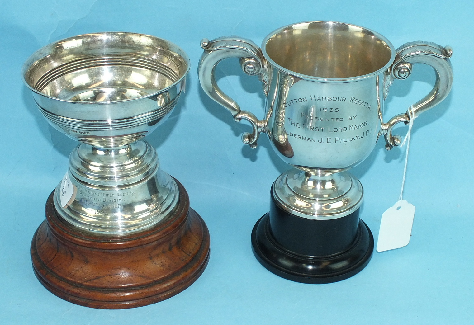 Lot 468 - A silver two-handled trophy cup with leaf-capped handles and spreading foot, on ebonised base,