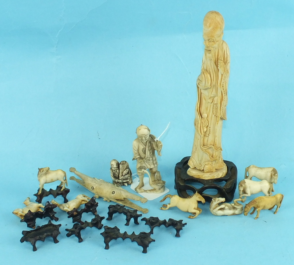 A Chinese ivory figure of a standing Immortal, 19cm high, two Japanese bone figures and a