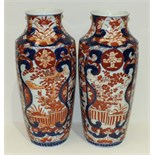 A pair of 19th century Japanese Imari vases decorated with flowers in a garden and a Kutani