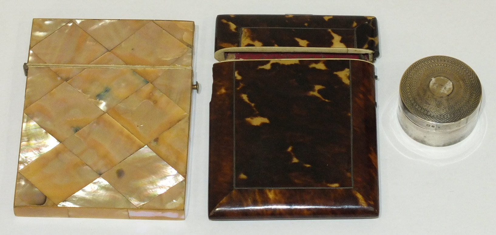 A mother-of-pearl card case, (a/f), a tortoiseshell card case, (a/f) and a circular silver pill box,