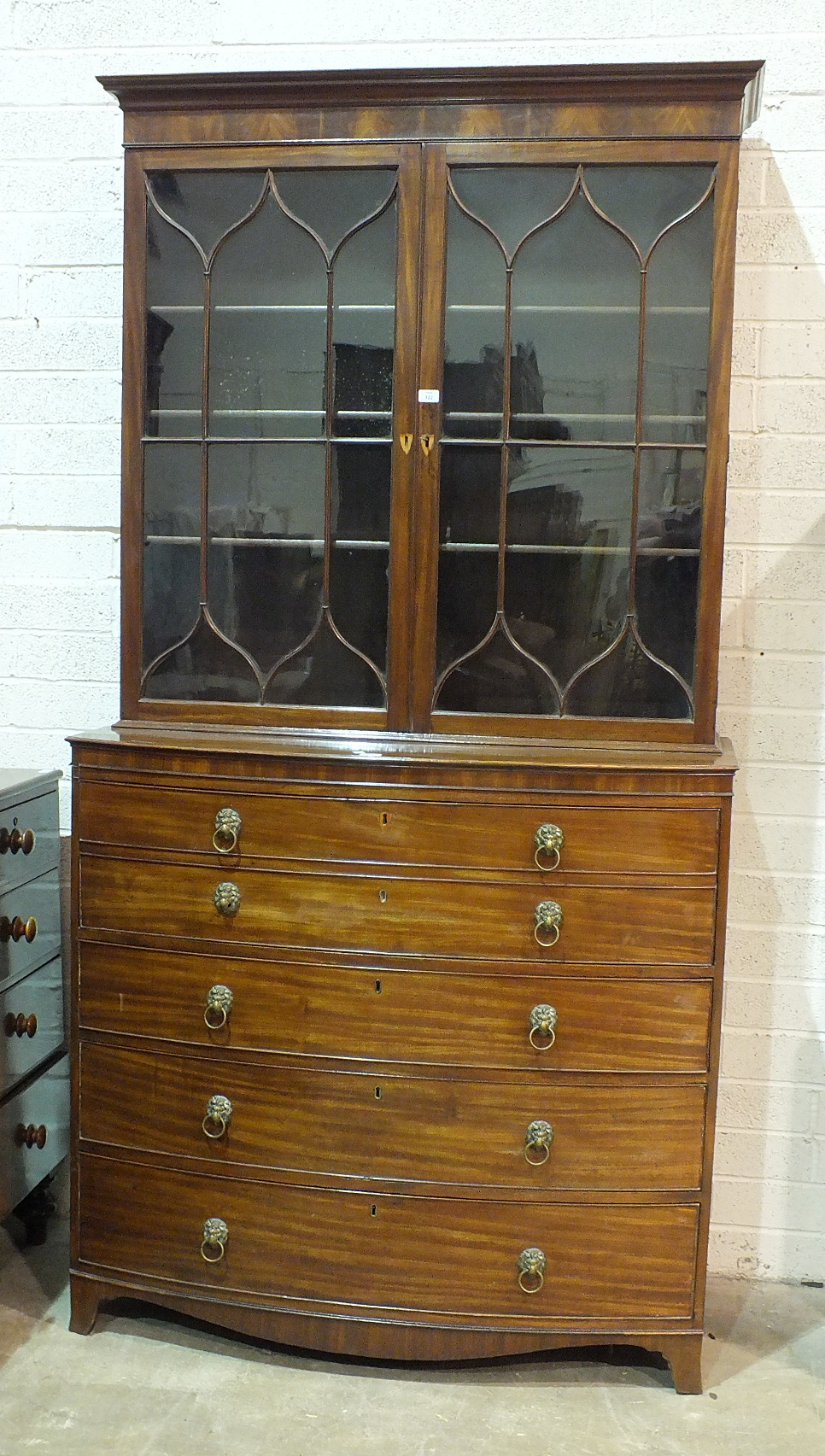 A George III mahogany bow-fronted secretaire bookcase, the moulded cornice above a pair of gothic