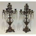A pair of early-20th century copper finish metal five-light candelabra adorned with cut glass drops,