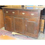 An antique oak dresser base, the rectangular top above two drawers and two cupboard doors, 140cm