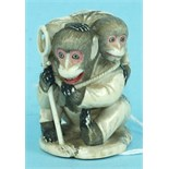 An ivory group of two monkeys playing, signed.