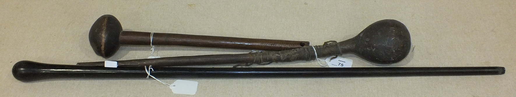 Two African throwing clubs and a hardwood walking cane, (3).