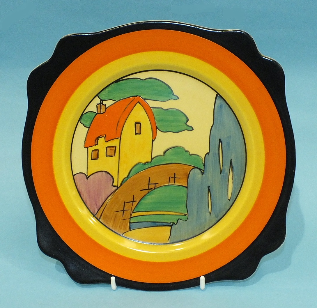 A Clarice Cliff shaped-rim plate decorated with the orange roofed cottage design, 25cm diameter.
