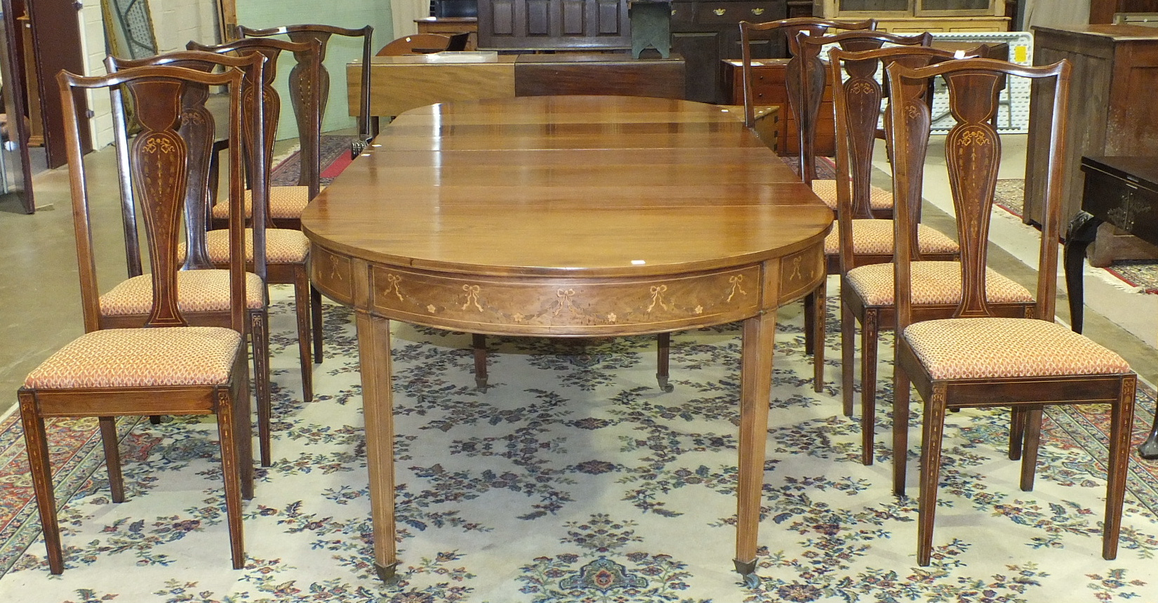 A Georgian-style pull-out dining table, the two 'D' ends above a frieze inlaid with ribbon-tied
