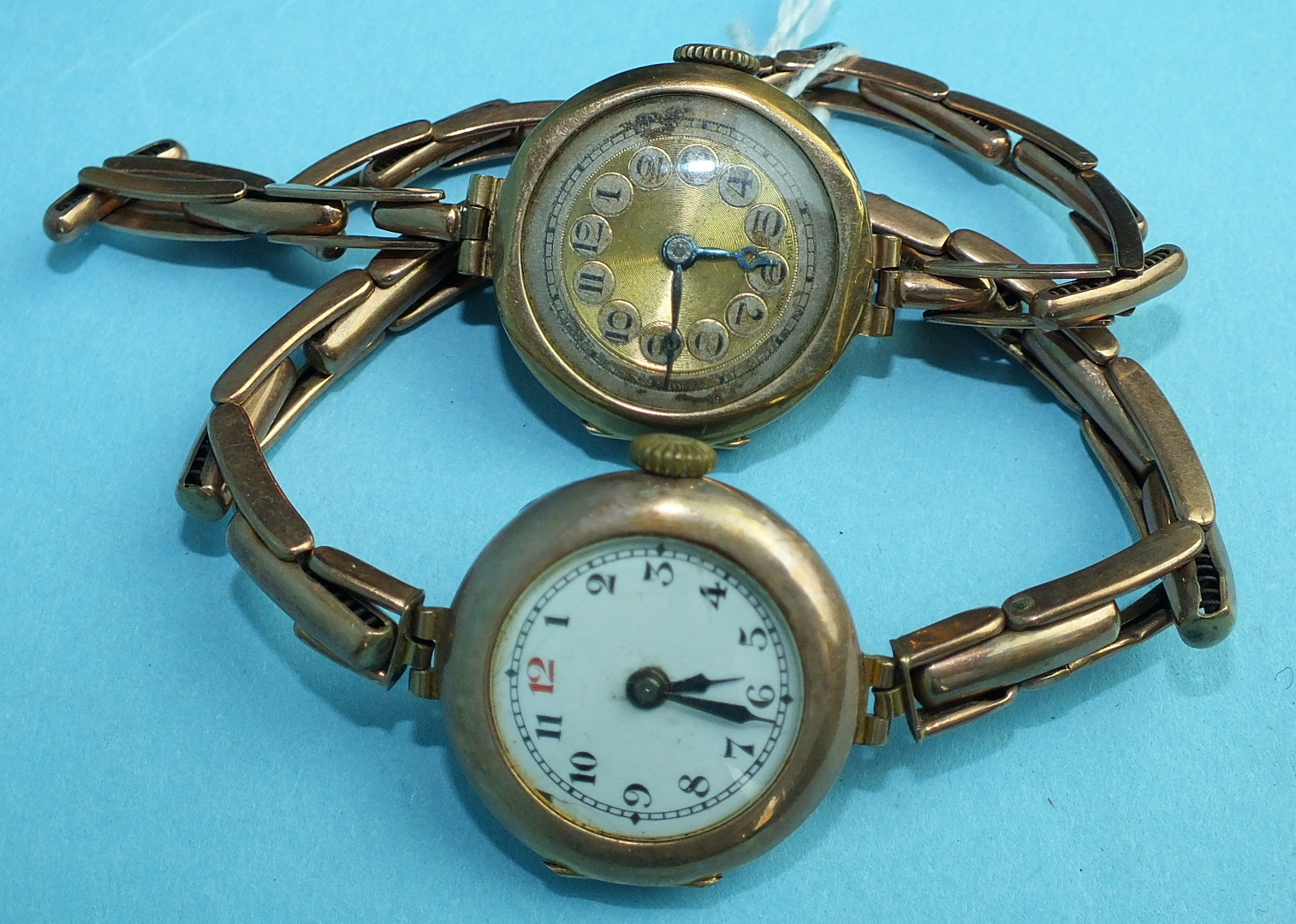 Lot 143 - Two ladies 9ct-gold-cased wrist watches on gold expanding bracelets, (2).