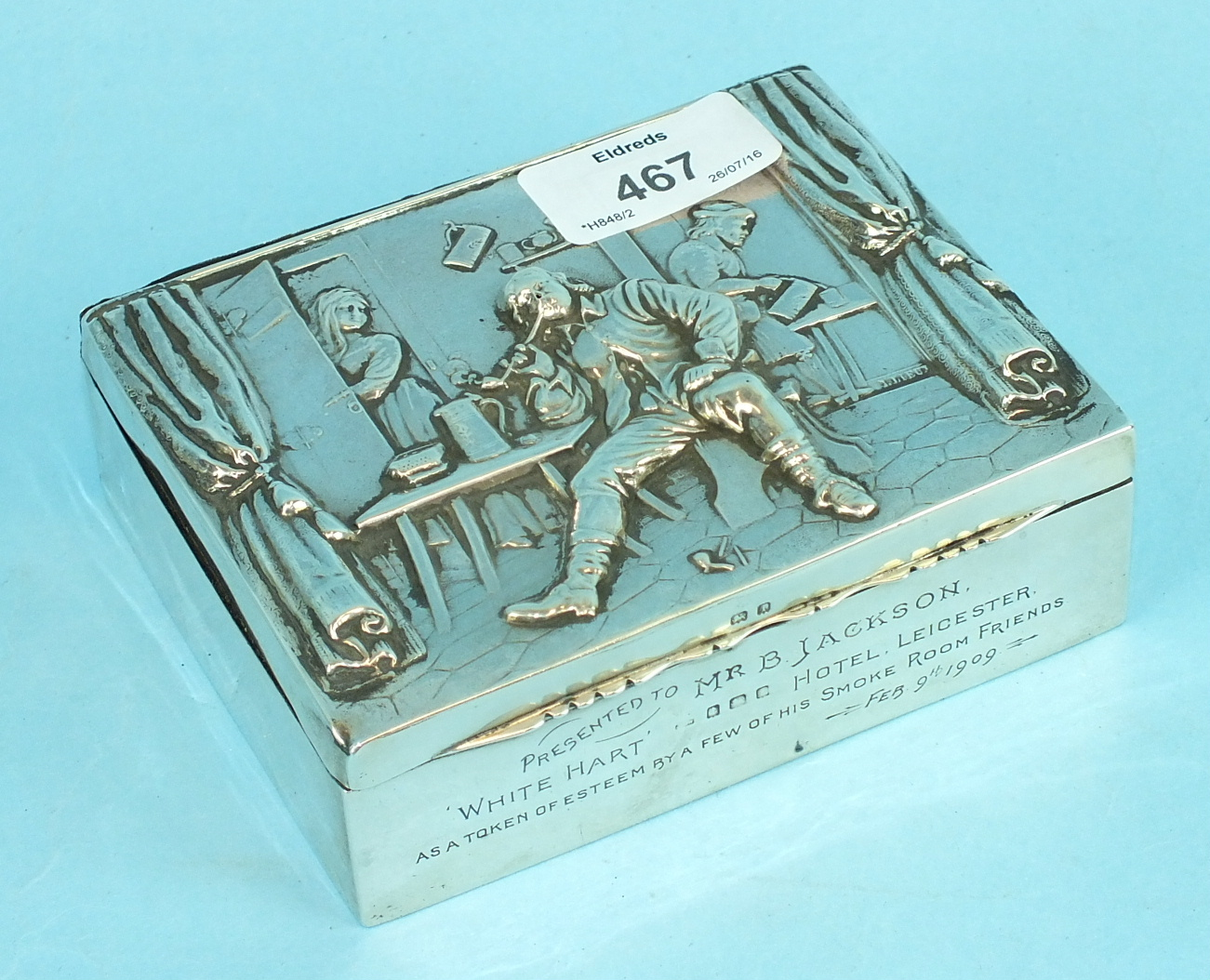 Lot 467 - An embossed cigarette box decorated with a tavern scene, presentation inscription to 'Mr B