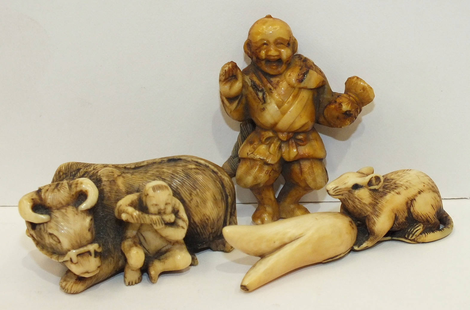 A 19th century Japanese ivory netsuke of a boy and a buffalo, (tail damaged), another of a rat
