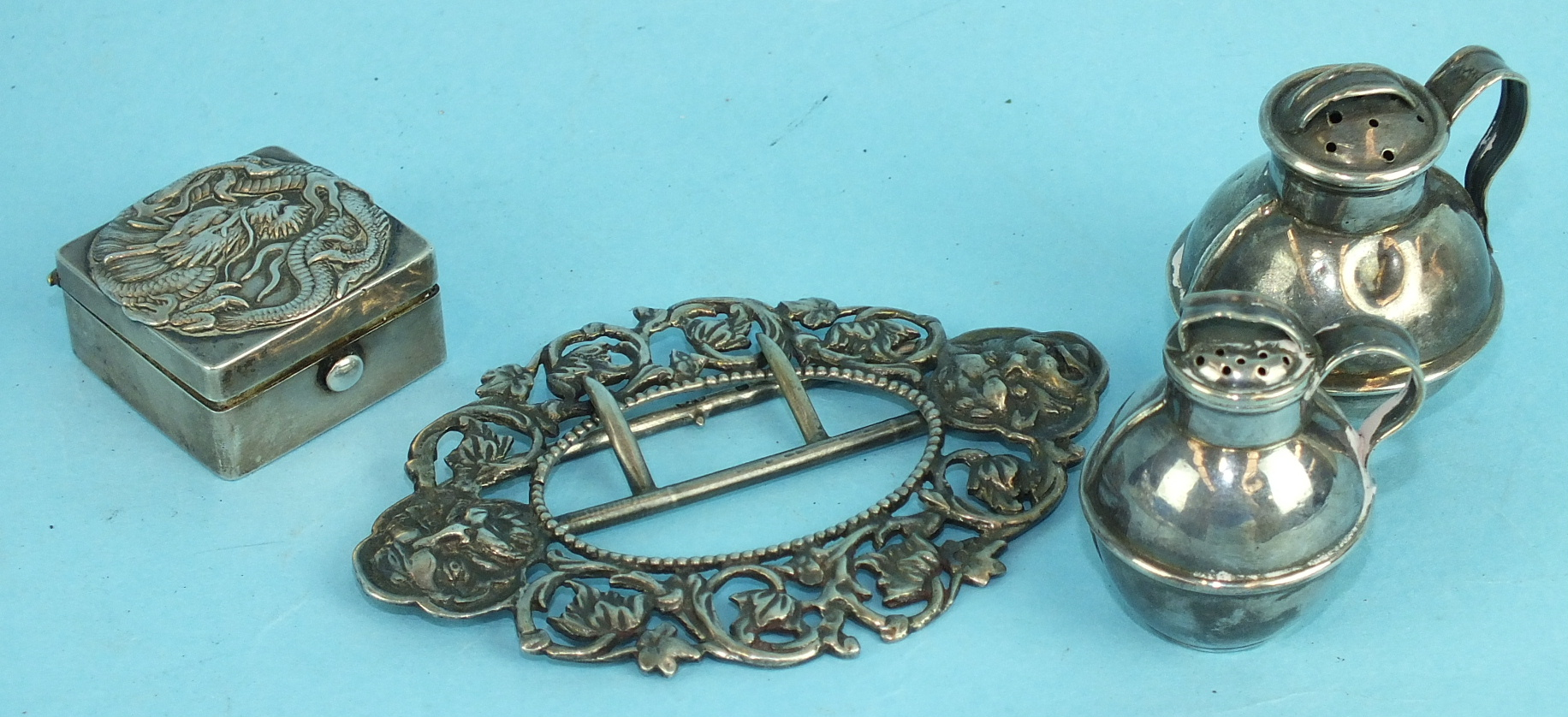 Lot 415 - A Chinese white metal pill box with raised dragon decoration, a silver belt buckle with cast mask