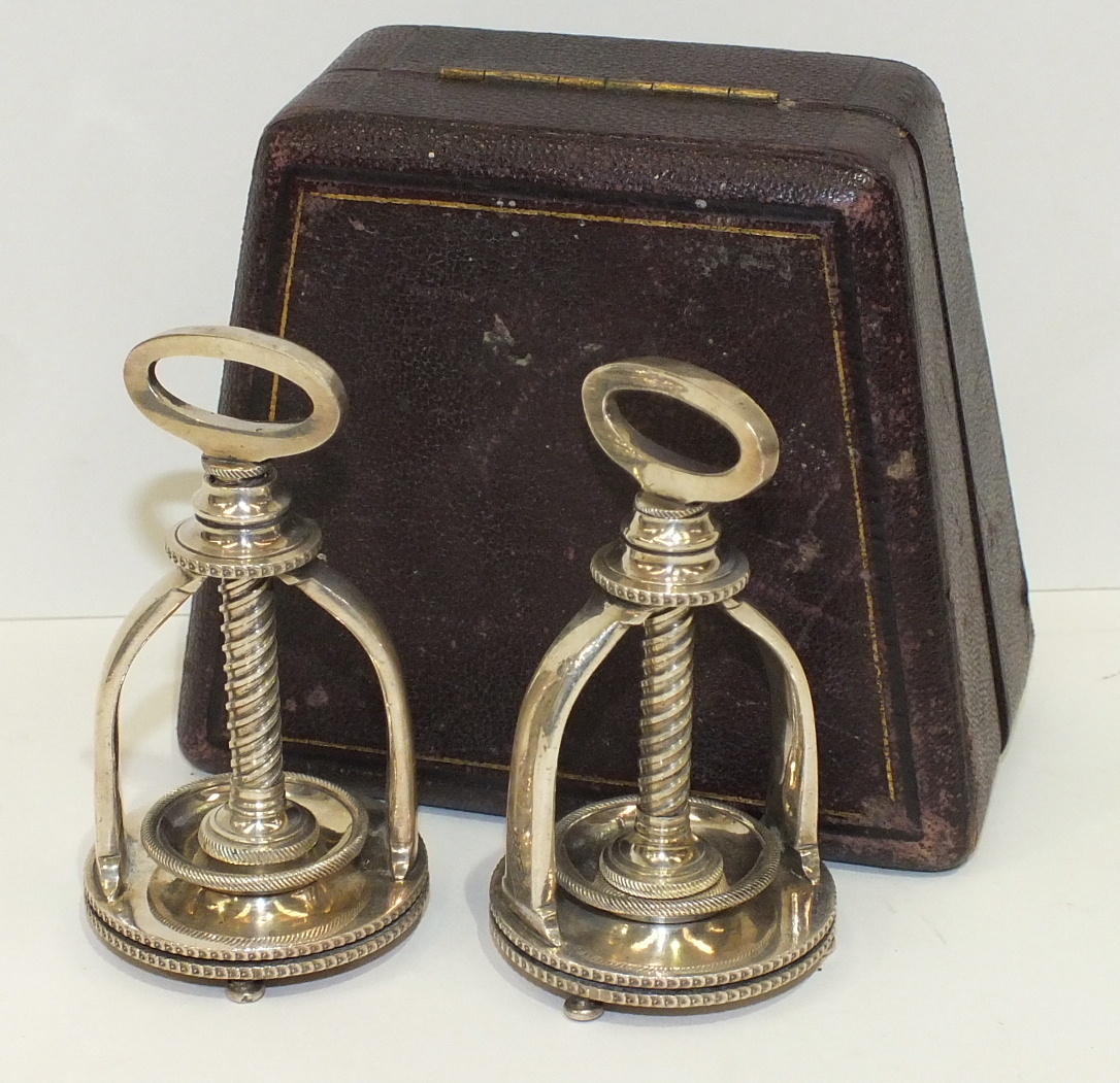 A pair of silver-plated mechanical presses, each with spiral rack acting on a small circular bowl